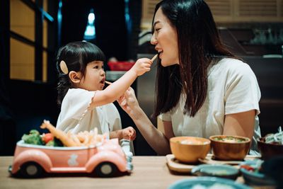 Young girl and mother feed each other french fries.