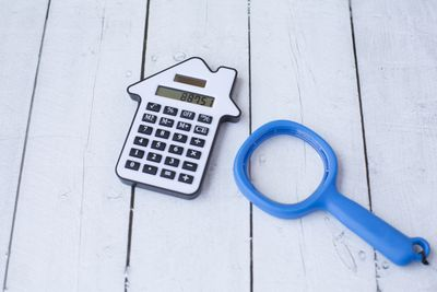 A calculator and a magnifying glass to signify figuring out a mortgage interest payment.