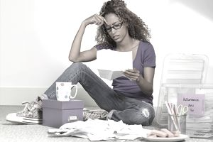 Frowning woman sitting on floor with coffee mug, papers, filing box, and cookies