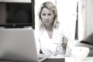 Woman checking laptop with cup of coffee in hand