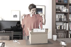 Woman looking at online purchased clothing at home