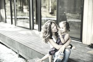 Smiling young girl sitting in mothers lap on porch of vacation home