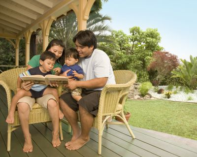 Young parents reading to two boys (1-3) on porch