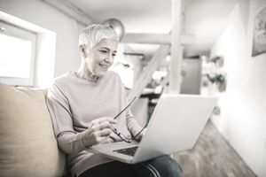 Happy mature woman looking at laptop