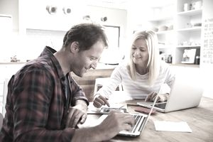 couple looking at laptops in kitchen