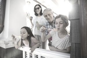 Multi-generation family blowing bubbles on summer porch