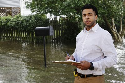 An insurance adjuster examines flood damage to a house.