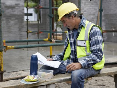 Builder eating packed lunch looks at documents on construction site