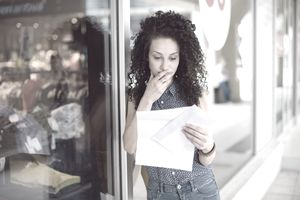 A concerned woman reads a notification of a pending job layoff as she leans against a store's window