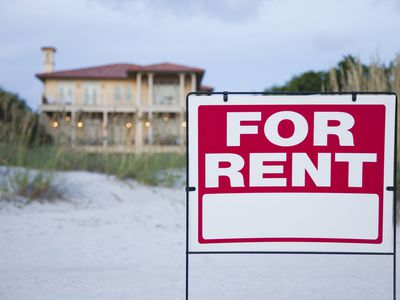 A for rent sign in front of large beach house after the owner could not sell.