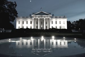 white house exterior at night reflected in a reflection pool