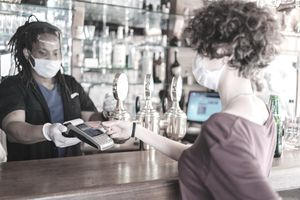 male bar owner doing contactless payment from customer - stock photo