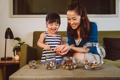 Mother counting coins into different savings jars with her child