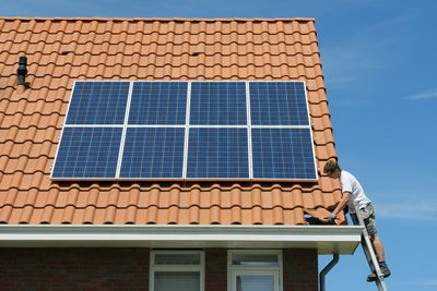 Worker checking installation of solar panels on roof of new home