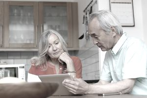 Retired couple looking at the stock allocation of their retirement portfolio while sitting at a kitchen table.