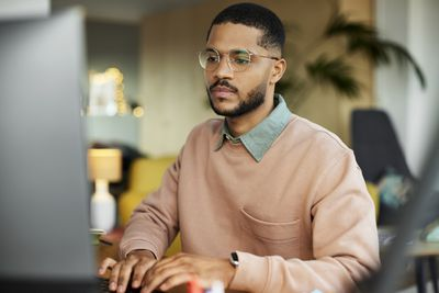 person in peach sweater wearing glasses looking at computer