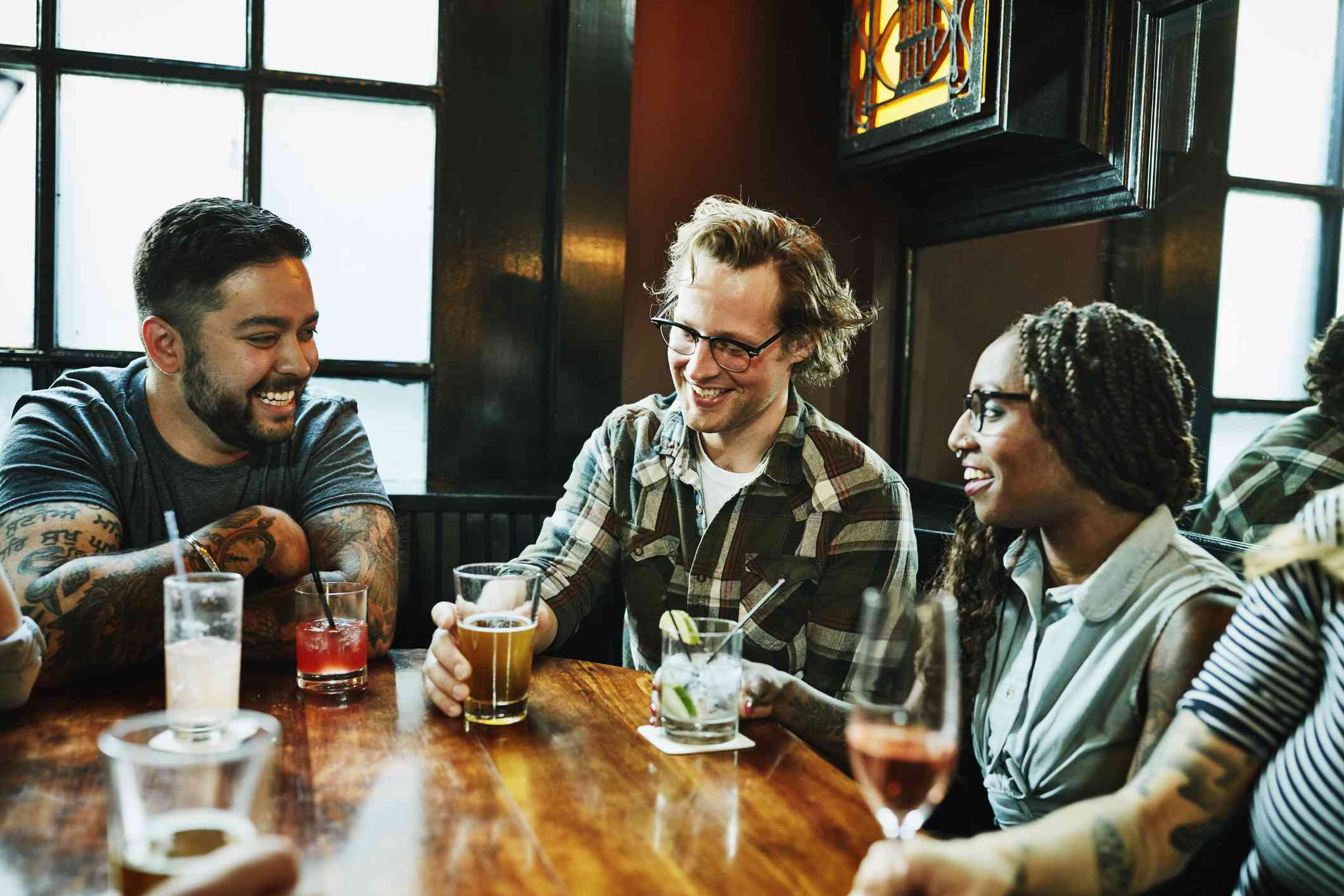 Laughing friends in discussion while sharing drinks at table in bar