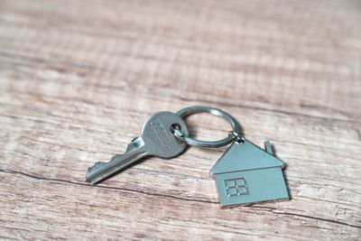 House key on a house shaped keychain resting on wooden floorboards concept for real estate, moving home or renting property