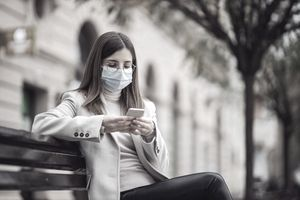 Young brunette with face mask on face sitting on the bench outside and using smart phone for texting.