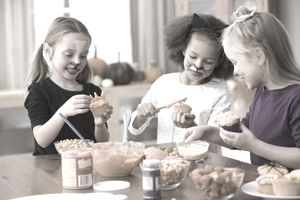 Three young girls putting frosting and candy on Halloween cupcakes at a kitchen table
