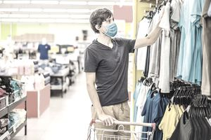 Man in a clothing store in a medical mask because of a coronavirus.