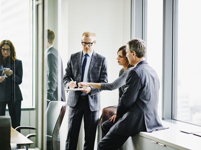 Business executives collaborating on project during informal meeting in office conference room