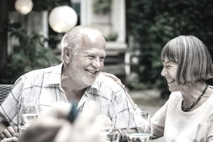 An older man and woman laugh while dining outside