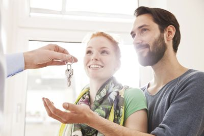 Happy young couple receives keys to their new home