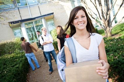 A young woman carrying a box in front of a building with other students