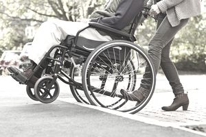 Woman pushing older man in wheelchair up step or ramp onto pavement