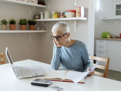 A mature woman reviews her retirement accounts on a laptop.