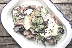 An enamel tray boasting an eggplant boat loaded with fresh roasted vegetables, salad and dips. Eggplant, carrots, avocado, red cabbage, cherry tomatoes, rocket, salad greens, coriander and topped with three types of hummus.