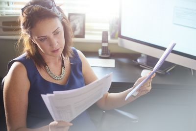 A woman in business attire sits at a desk reviewing documents.