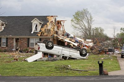 A smashed and overturned SUV lies on the lawn in front of a wind-damaged home.