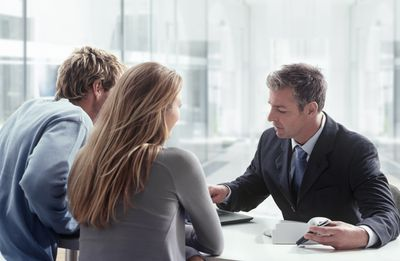 Young couple at a desk meeting with a businessman over paperwork