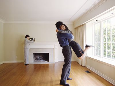Couple embracing in new home, realtor in background