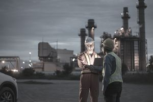 engineer using digital tablet working late night shift at petroleum oil refinery in industrial