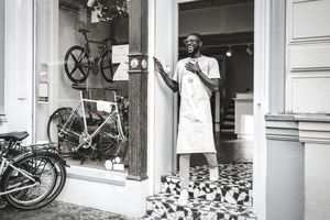 Bicycle shop employee in apron smiles at store entrance