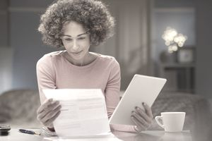Woman looks at federal loan statement while holding a tablet and leaning on a countertop.