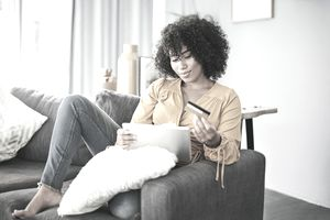 Full length shot of an attractive young woman sitting on her home sofa and using her tablet for online shopping