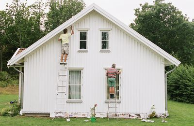 Men in shorts painting house an HOA-approved color