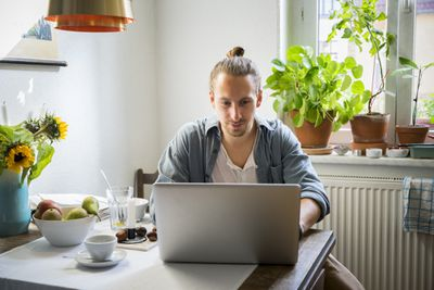 Person with hair in bun using laptop at kitchen table