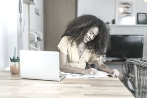 Smiling young woman writing on paper at dining room table