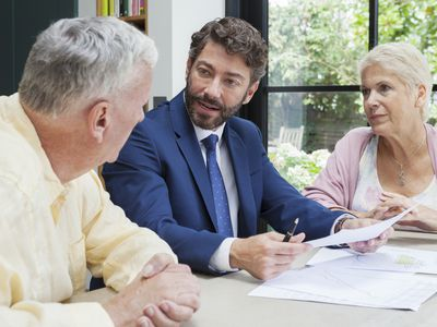 Financial advisor meeting with senior couple in kitchen