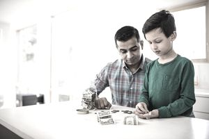 A father and son count change on the kitchen counter after they have placed a freeze on the child's credit