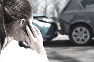 Woman on phone with her car insurance provider with a fender bender in the background