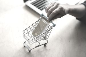 Hand pushing a mini shopping cart that holds a credit card across a desk