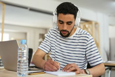 Young man in striped shirt wearing headphones taking notes at desk in office