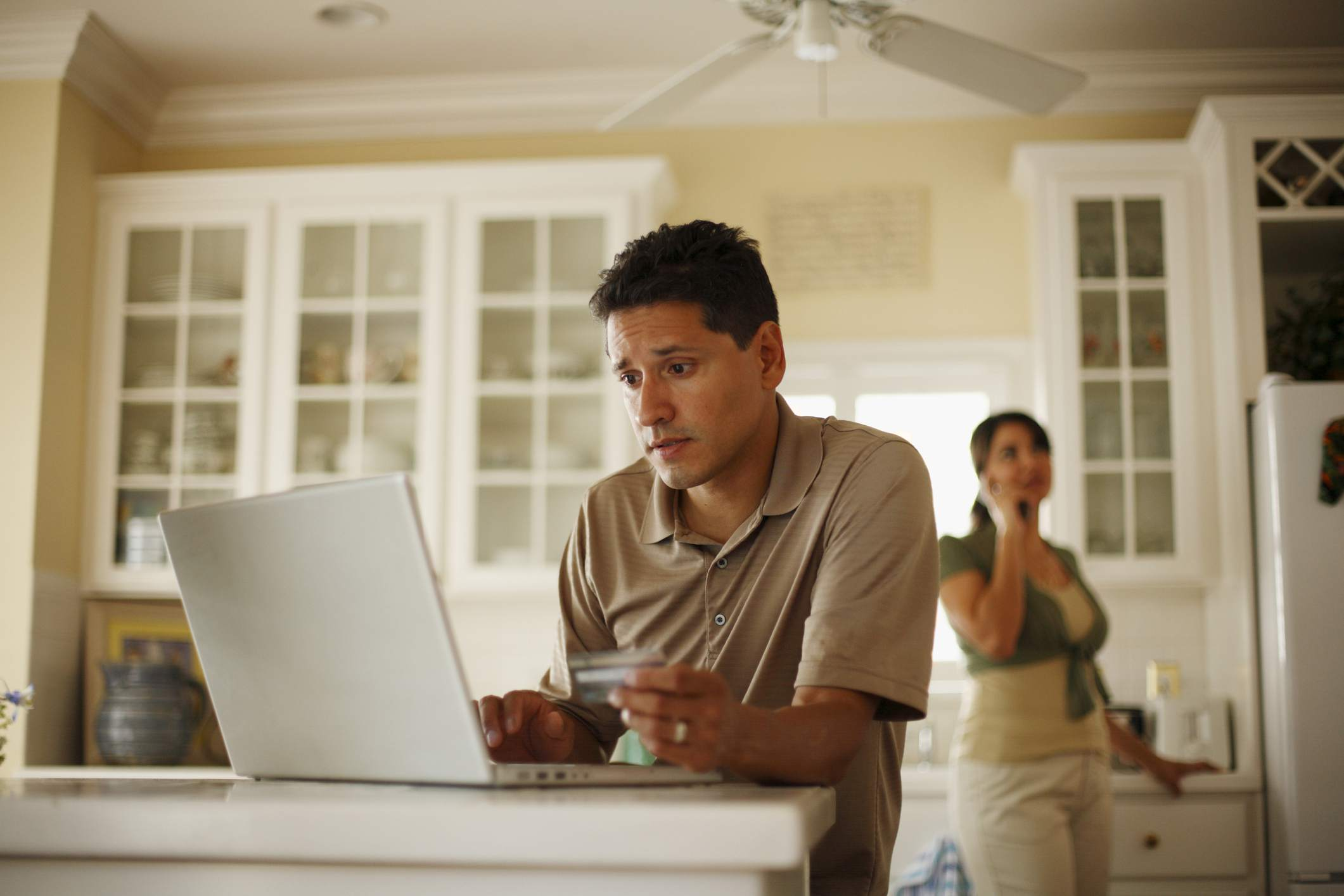 A man looking over his investments on a laptop