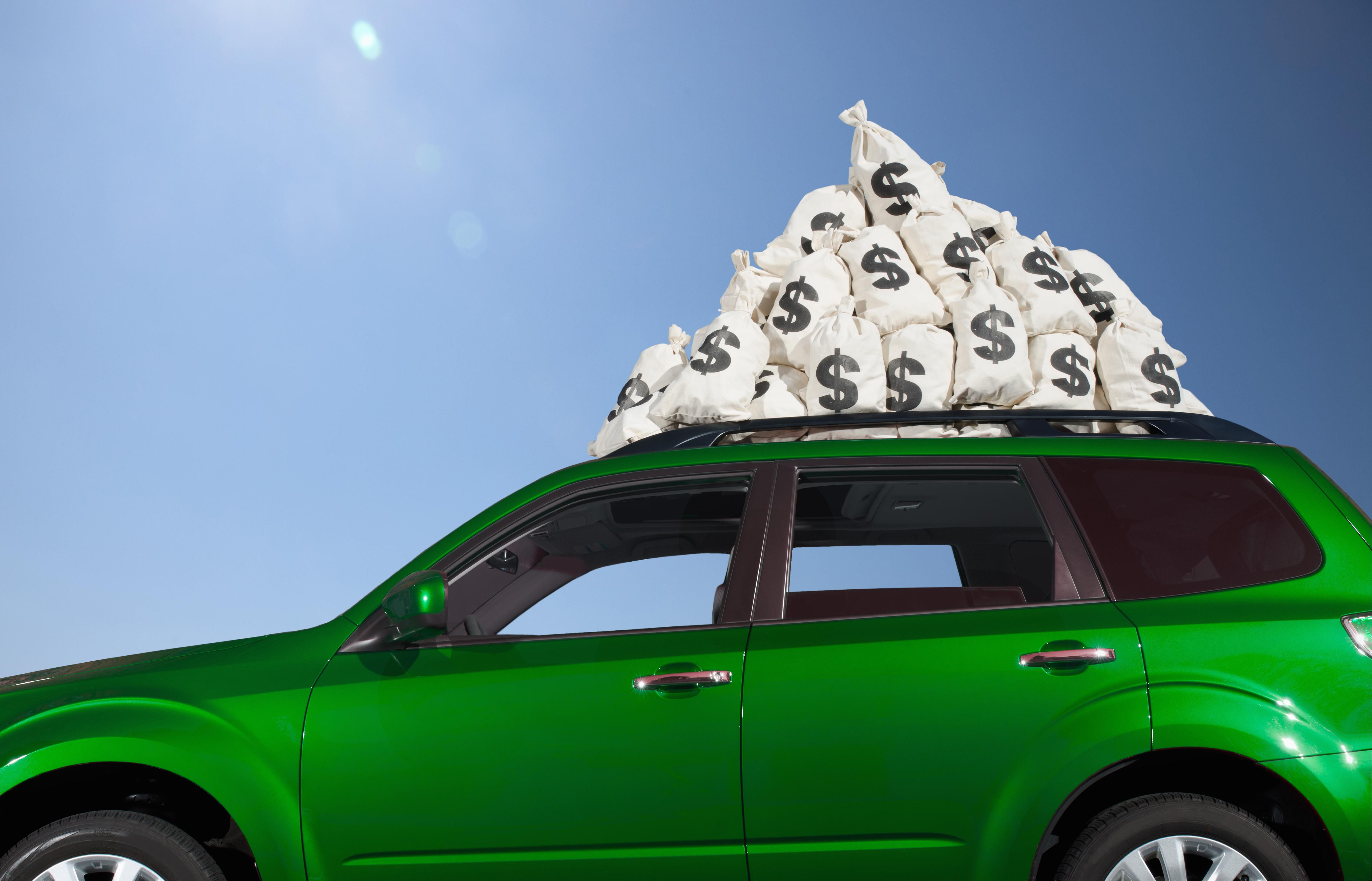 Money bags piled on car roof